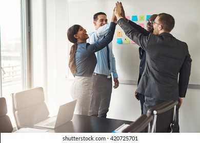 Successful diverse multiracial business team giving a high fives gesture as they celebrate in a conference room in an office