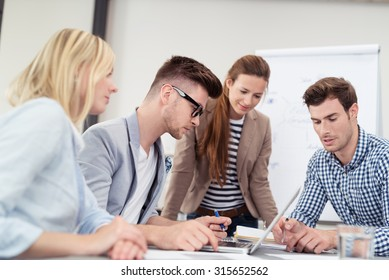 Successful diverse young business team working together on a project grouped around an office table in a teamwork concept