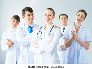 successful doctor, accepts congratulations from colleagues, stand behind him and clap