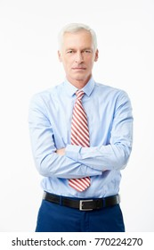 A successful elderly man with arms crossed standing at isolated white background and looking at you.