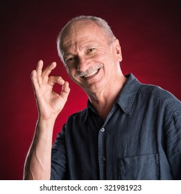 Successful elderly man showing ok sign  on a red background