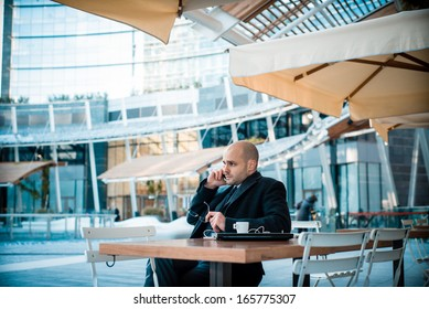 successful elegant fashionable businessman on the phone at the bar