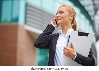 Successful employee or manager talking on cellphone outside