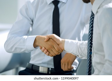 successful employees shaking hands sitting at the Desk