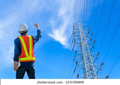 Successful engineers stand against high voltage poles on a blue background.