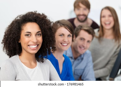 Successful enthusiastic multiethnic business team led by a beautiful young African American businesswoman posing together in a row with focus to the woman