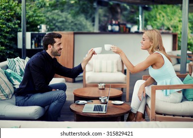 Successful entrepreneurs clinking cups for toast successful adoption of the agreement, business partners smiling while drinking coffee while discussing good idea, business people enjoying coffee break