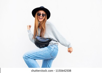 Successful  exited stylish girl with candid smile posing on white urban wall, wearing grey sweater and jeans.