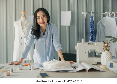 Successful fashion designer. Full length of attractive young asian woman looking at camera with smile while standing in workshop. Beautiful owner business woman working in studio .