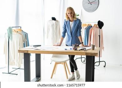 Successful fashion designer. happy casual trendy caucasian blonde fashion designer businesswoman in workshop