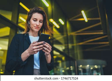 Successful female banker using smartphone outdoors while standing near office background yellow neon lights, young woman professional manager working on mobile device near skyscraper at night