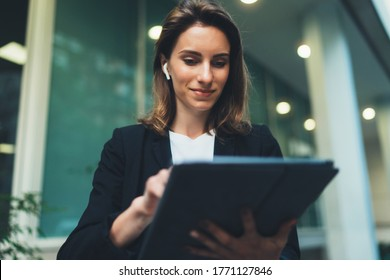Successful female banker using tablet and wireless earphones outdoors near his office background lights, portrait young woman professional manager working on touch pad near skyscraper in evening city