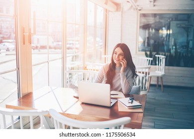 Successful female IT developer working online at cozy cafeteria using laptop computer while calling via new smartphone app for conversation with friend indoors, concept of technology and communication