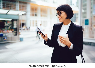 Successful female entrepreneur with coffee to go in hands checking email on smartphone via high speed 4G internet walking in New York street. Businesswoman using banking application in mobile phone