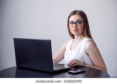 Successful female grapic designer watching tutorial about creative ideas at laptop computer during working process in office.Positive student with blonde hair reading business news on netbook