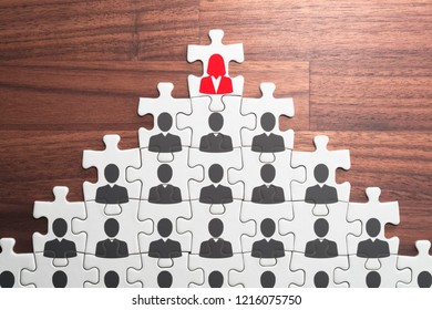 Successful female leader and corporate hierarchy.Human resource management and leadership concept. Assembling jigsaw puzzle on wood desk.