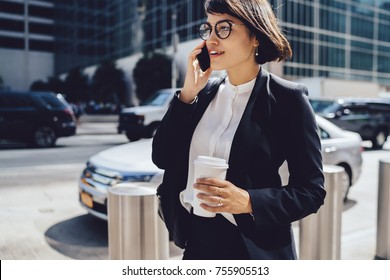 Successful female manager in elegant wear walking on city street and talking on mobile, prosperous businesswoman having phone conversation about work holding coffee to go with copy space for brand nam