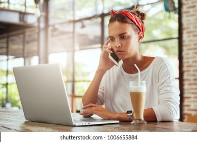 Successful female project manager looks with serious expression in notebook, arranges meeting with partner via cell phone, works in coffee shop, has tasty milk cocktail. Communication concept