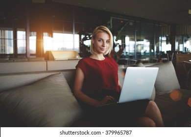 Successful female restaurateur with laptop computer waiting for business partners while sitting in office interior, young woman employer posing during work on net-book in modern comfortable cafe