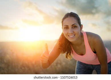 Successful female runner taking a rest during outdoor running workout at sunset. Female athlete doing success thumbs up geture. Sport and exercise motivation concept.