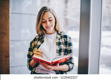 Successful female student reading positive bestseller at university library, happy smiling hipster girl casual dressed enjoying literature indoors, caucasian woman searching information in book