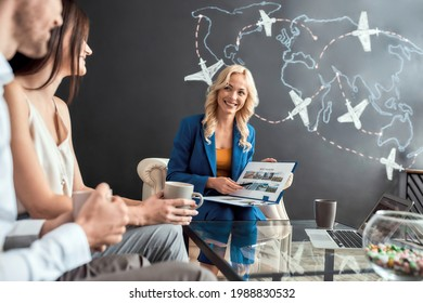Successful female travel agent smiling while showing catalog with tours to happy young couple, sitting in modern office and drinking coffee. Tourism, travelling, business concept