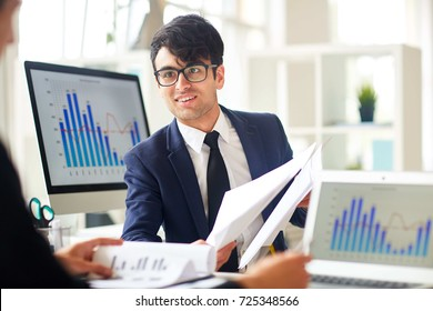 Successful financier showing some papers to co-worker during discussion