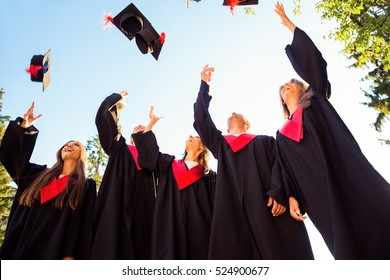 Successful five students with congratulations together throwing graduation hats in the air and celebrating.