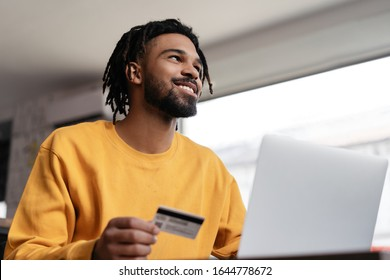 Successful freelancer receive payment. Happy African American man holding credit card, using laptop computer for online shopping.  Pensive hipster ordering food online, booking tickets and smiling
