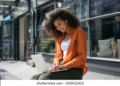 Successful freelancer typing on keyboard using laptop computer. Portrait of cheerful woman copywriter working project. Smiling African American student studying, learning language. Online education