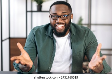 Successful friendly multiracial black male freelancer, business leader or tutor, speaking during video conference with colleagues or friends, gesturing hands and smiling, talks about plans,strategy