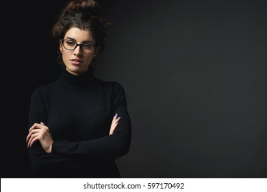 A successful girl in glasses and dressed in black golf stands on a dark background and looks away. Fashion photo for magazine or article