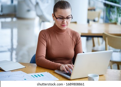 Successful girl manager in her own office with large windows makes a new economic development business plan on a laptop with a cup of coffee. A business woman with documents sits at a wooden table