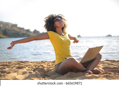 Successful girl working at the beach and relaxing