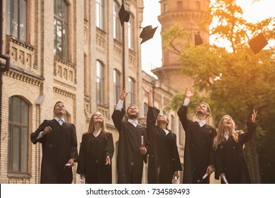 Successful graduates in academic dresses are holding diplomas, throwing their caps and smiling while standing outdoors