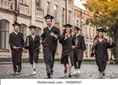 Successful graduates in academic dresses are holding diplomas, looking at camera and smiling while running outdoors