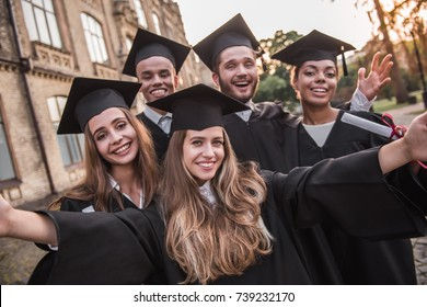 Successful graduates in academic dresses are holding diplomas, looking at camera and smiling while standing outdoors