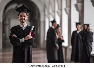 Successful graduates in academic dresses are talking in university hall, guy in the foreground is holding diploma, looking at camera and smiling