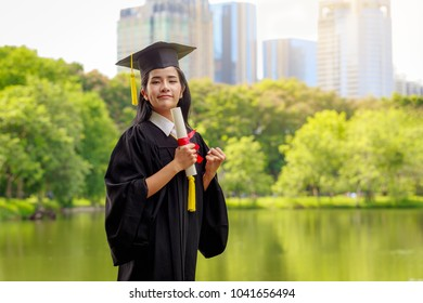 Successful graduating student wearing cap and gown holding diploma, Education concept