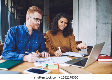 Successful graphic designers creating new logo for company during collaboration in coworking space, positive multicultural male and female hipsters enjoying time for cooperation on laptop device