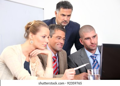 Successful group of business colleagues working on a laptop