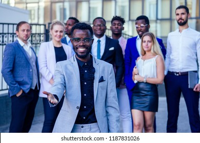 successful and handsome African American man in a stylish business suit giving a hand for a handshake sign welcome ahead of a group a lot of people multiracial multiethnic company