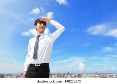 Successful handsome business man purposefully looking away with blue sky and city background, mode is a asian male