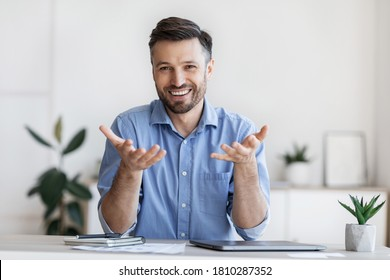 Successful handsome businessman sitting at desk in office, talking at camera, sharing his experience and ideas, free space