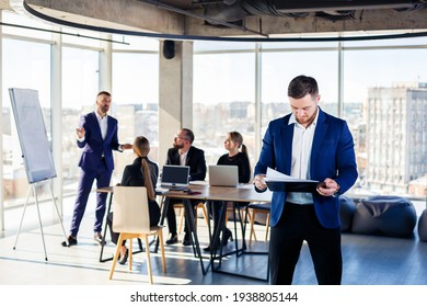 Successful handsome male mentor, director, businessman in a suit at the office. Working day concept. Team meeting with the boss in the foreground
