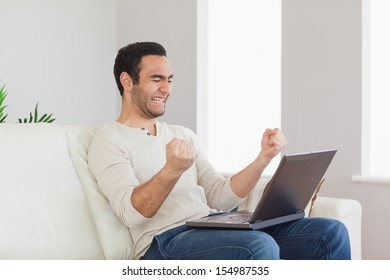Successful handsome man looking at his laptop while sitting in bright living room