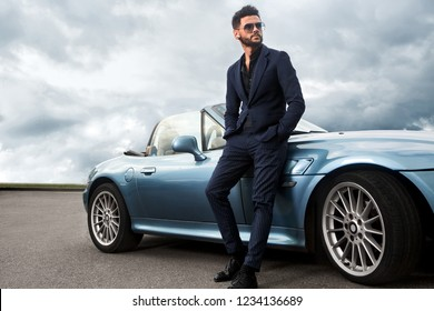 Successful, handsome man near the car.