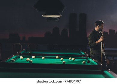 successful handsome man standing beside pool table at bar