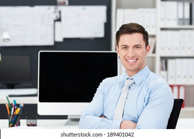 Successful handsome young businessman with a happy smile sitting at his desk in the office with folded arms