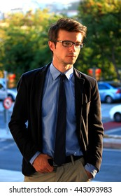 Successful handsome young businessman wearing glasses outdoors